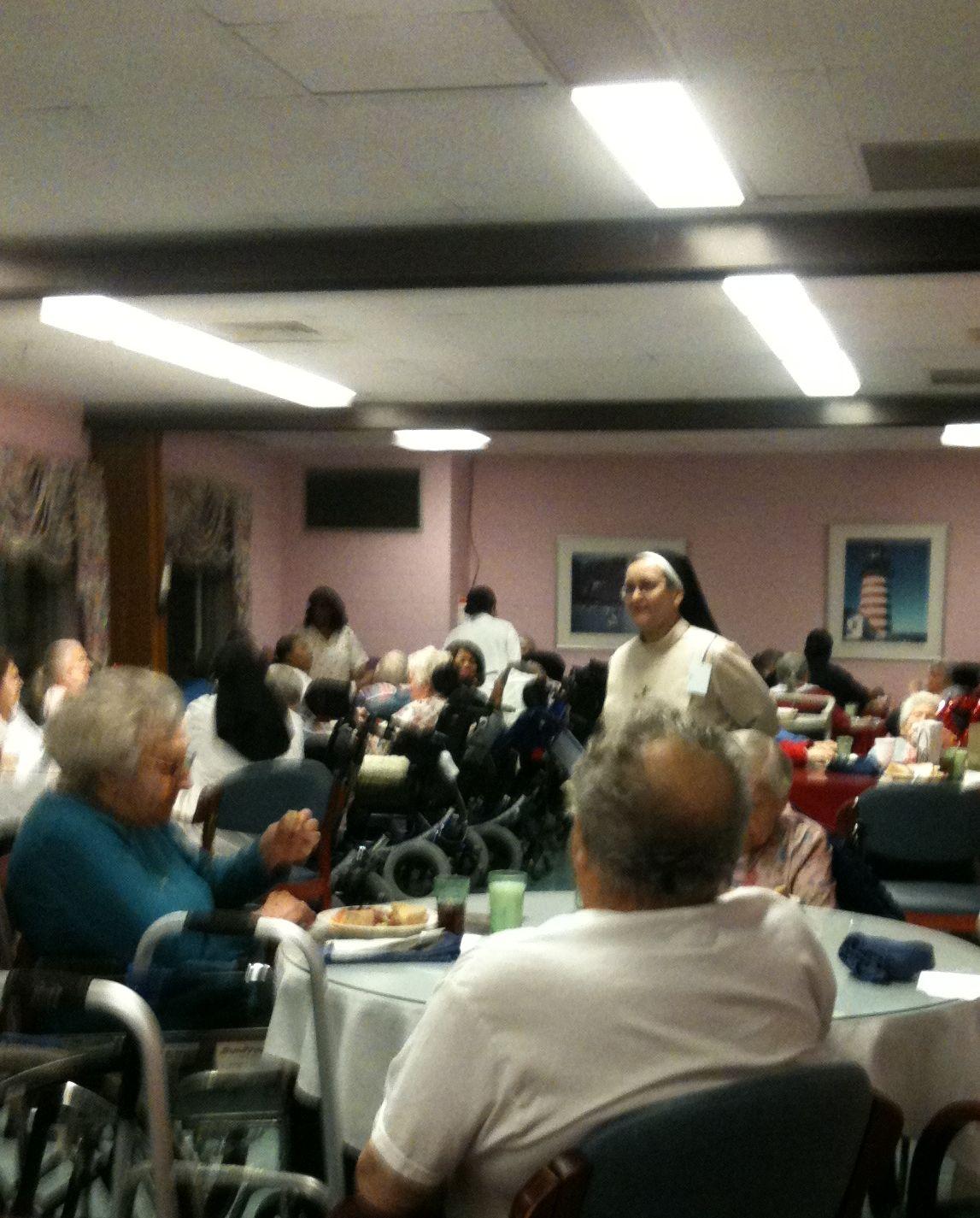 Religieuse parmi les patients dans la salle à manger
